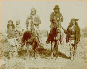 Geronimo (left) and Naiche (right) on horseback. Geronimo's son standing beside him.