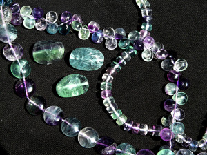 Semi-precious beads cut from clear, purple, green, and blue Fluorite